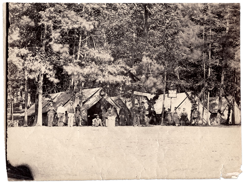 """View of the USCC station at Gettysburg: Though this albumen is not credited, a print of the same scene with the Tyson Brothers' imprint (Charles J. and Isaac G.) is in the collections of the New York Public Library. A third print, in the Adams County Historical Society, is marked """"488, Convalescents at General Hospital."""" W.H. Tipton, who had apprenticed with the Tyson Brothers, made a variation of this scene, with the subjects posed differently, into a stereoview. Author's collection."""